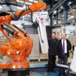 Директора Northern Paper Board Джон, слева, и Пол Карран с одним из недавно установленных автоматизированных роботов компании.